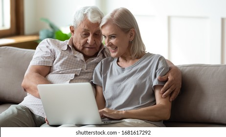 Smiling older wife and husband hugging, using laptop, sitting on cozy couch, watching movie or shopping online, looking at screen, mature man and woman spending leisure time together at home
