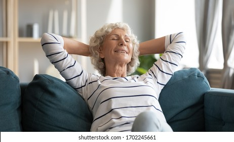 Smiling older woman leaning back, relaxing on cozy couch, happy mature senior female with hands behind head sitting on sofa in living room, daydreaming with closed eyes, lazy peaceful weekend