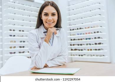 smiling optician with papers and pen looking at camera in ophthalmology