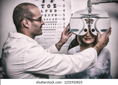 Smiling optometrist examining female patient on phoropter in ophthalmology clinic