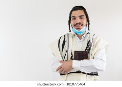Smiling orthodox jewish man looks at camera, wearing protective mask against covid-19 pandemic.