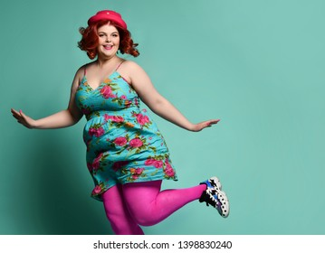 Smiling overweight fat chubby woman in funny hat and colorful clothes jumps or tries to fly like a little bird on popular mint background with free text copy space