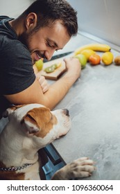 Smiling owner looking at his pit bull in the kitchen while he stands up