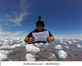 Smiling parachutist holding a written sign: Welcome 2021.