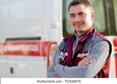 Smiling paramedic with folded arms on ambulance machine background