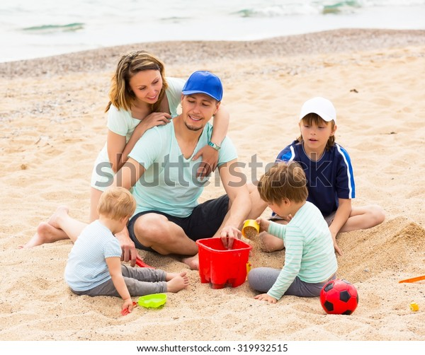 Smiling parens with kids having a rest on sandy beach