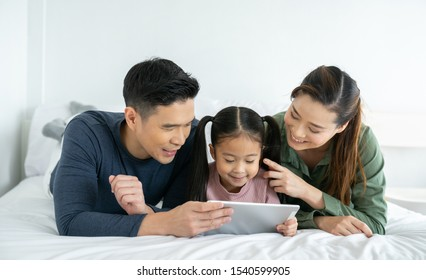 Smiling parents and child are very happy, using digital tablet in living room at home