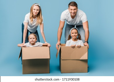 smiling parents with children in cardboard boxes for relocation on blue