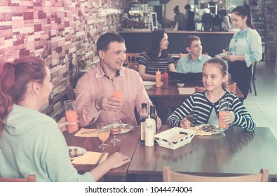 Smiling parents with children having conversation at dining table in cafe