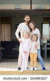 Smiling parents and children looking at camera standing on big house terrace, happy couple with kids spending leisure time outside home, luxury real estate, family mortgage concept, vertical portrait