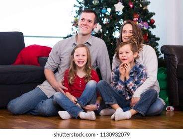 smiling parents and children posing for photo by Christmas tree at home