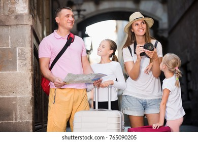 Smiling parents with  children using map and photographing sights during their vacation