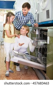 Smiling parents with daughter choosing dishwashing machine in home appliance store. Focus on woman