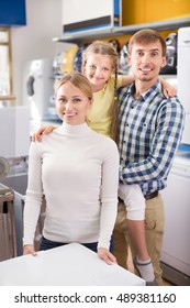 Smiling parents with daughter standing at a home appliance store. Focus on woman