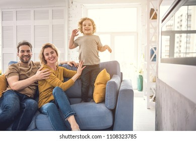 Smiling parents are embracing on cozy couch and looking at camera with joy. Joyful son is standing on sofa while mother is carefully holding him. Happy spouse with child concept