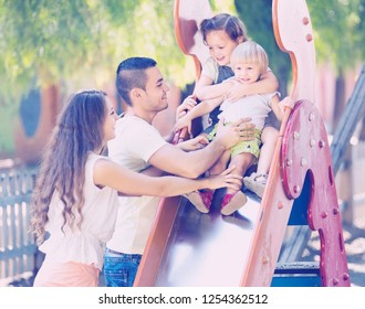 Smiling parents helping two girls  on slide in summer day