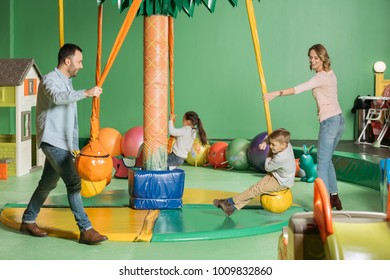 smiling parents looking at happy kids swinging on swings in indoor play center