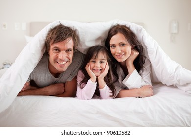 Smiling parents lying under a duvet with their daughter in their bedroom