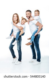 Smiling parents piggybacking happy children isolated on white