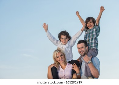 Smiling parents with playful kids outdoors