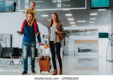 Smiling parents with son are walking with luggage at airport. Kid is riding on dad shoulders and hugging parent while mother is carrying documents and tickets. Copy space in right side