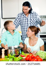 Smiling parents with teenager son cooking vegetarian lunch in home kitchen