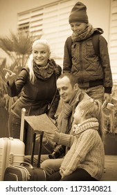 Smiling parents with two children and baggage checking direction with urban map