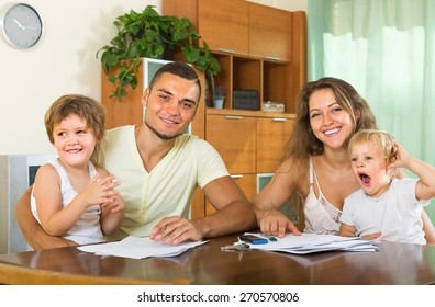Smiling parents and two little daughters sitting at table with documents