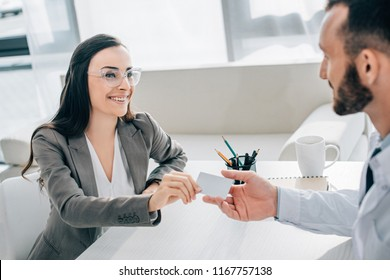 smiling patient giving id card to doctor in clinic
