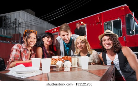 Smiling patrons at table in front of chef and food truck