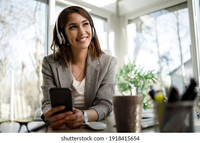 A smiling pensive woman using smartphone while working in her home office.