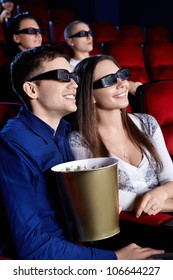 Smiling people in the 3D glasses at the cinema
