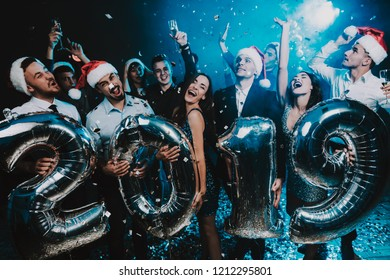 Smiling People with Baloons Celebrating New Year. Celebrating of New Year. Young Woman in Dress. Young Man in Suit. Santa Claus Cap. People with Gray Baloons. Happy New Year. People Have Fun.
