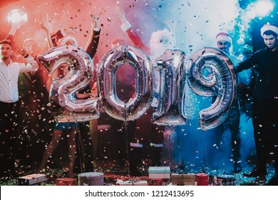 Smiling People with Baloons Celebrating New Year. Celebrating of New Year. Young Woman in Dress. Young Man in Santa Claus Suit. People with Gray Baloons. Happy New Year. People Have Fun.