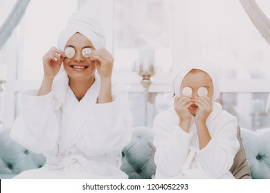 Smiling People in Beauty Salon. Mother and Daughter in Spa. Consept Beauty Salon. Beautiful Face. Woman and Happy Child. Woman with Curlers. Doing Selfie. Blue Sofa in Spa Salon. White Interior.