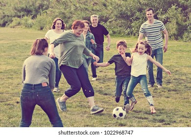 Smiling people of different ages playing football on grass