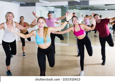 Smiling people of different ages studying zumba dance elements in dancing class