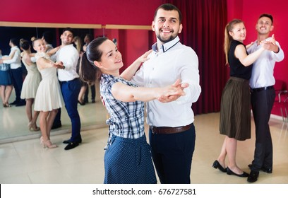 Smiling people learning to dance waltz in dancing class