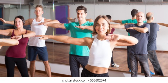 Smiling people learning zumba steps in dance hall