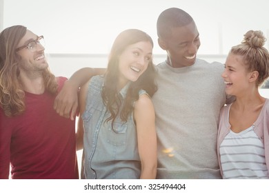 Smiling people looking at each other with arms around