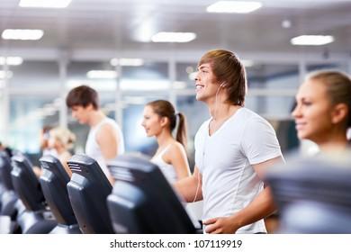 Smiling people on treadmills at fitness club