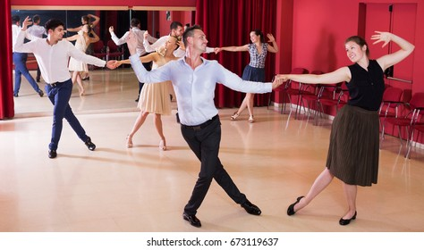 Smiling people practicing vigorous lindy hop movements in dance class