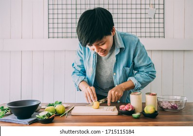 Smiling people are slicing lemons on a table with vegetables,chives, lemongrass, kaffir lime leaves to make canned fish salad menu Is simple menu. Thai food. Cooking preparation in the kitchen at home