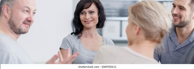 Smiling people talking with psychologist during group therapy