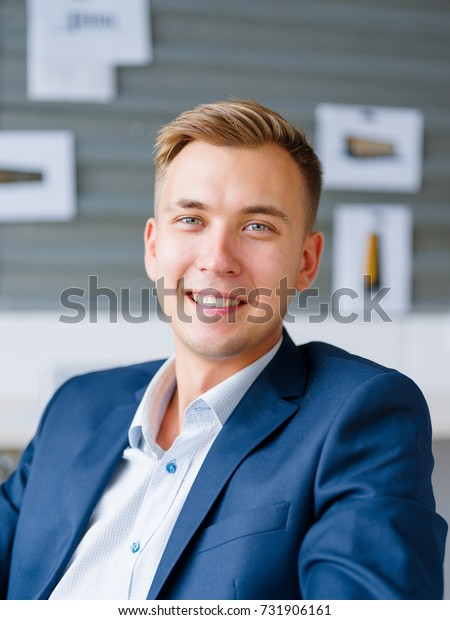 Smiling, perfect young man in a suit on a blurred background. Business success concept.