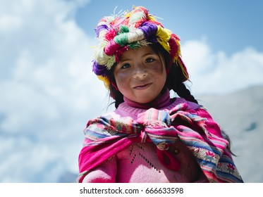 Smiling peruvian girl dressed in colourful traditional handmade outfit. October 21, 2012 - Patachancha, Cuzco, Peru