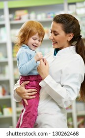 Smiling pharmacist chemist woman playing with child girl in pharmacy drugstore