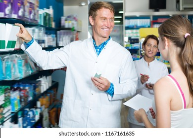 Smiling pharmacist wearing white coat helping customers in drug store