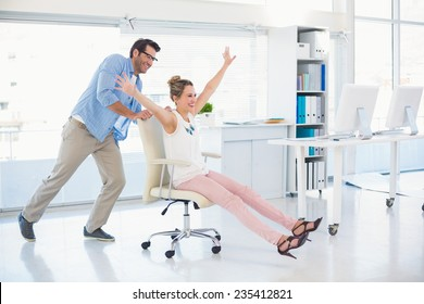 Smiling photo editors having fun with on a swivel chair in office
