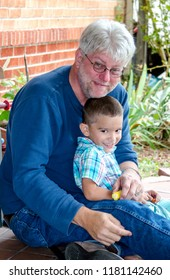 smiling photo of  grandchild sitting on grandpa's lap outdoors